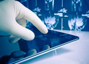 Hand In Medical Blue Glove Touching Modern Digital Tablet On X-r